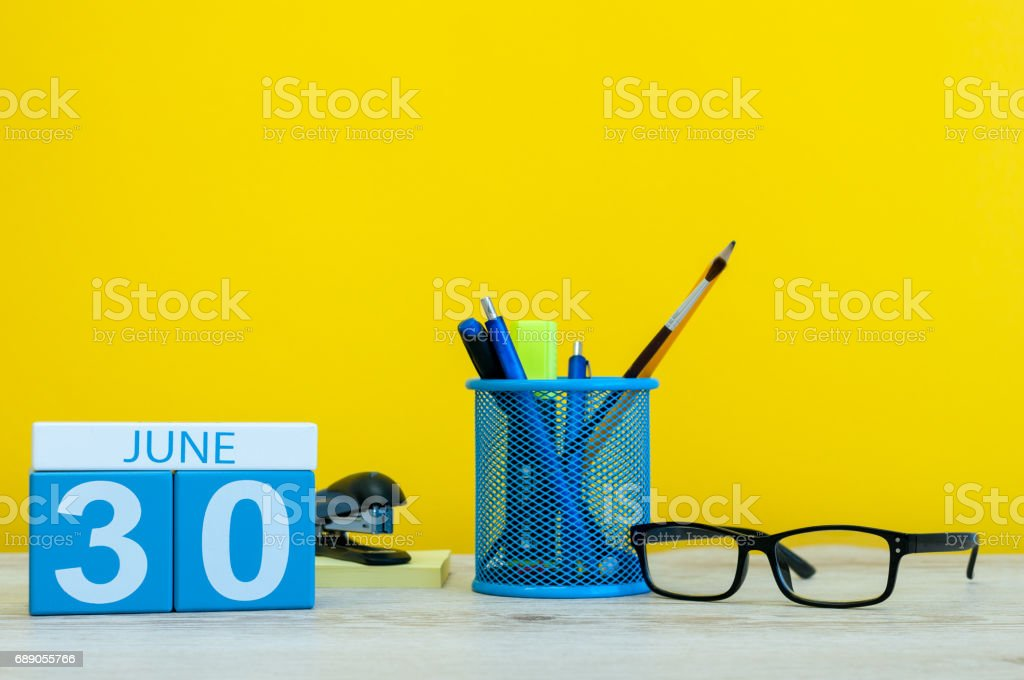 June 30th. Day 30 of month, calendar on yellow background with office suplies. Summer time at work stock photo