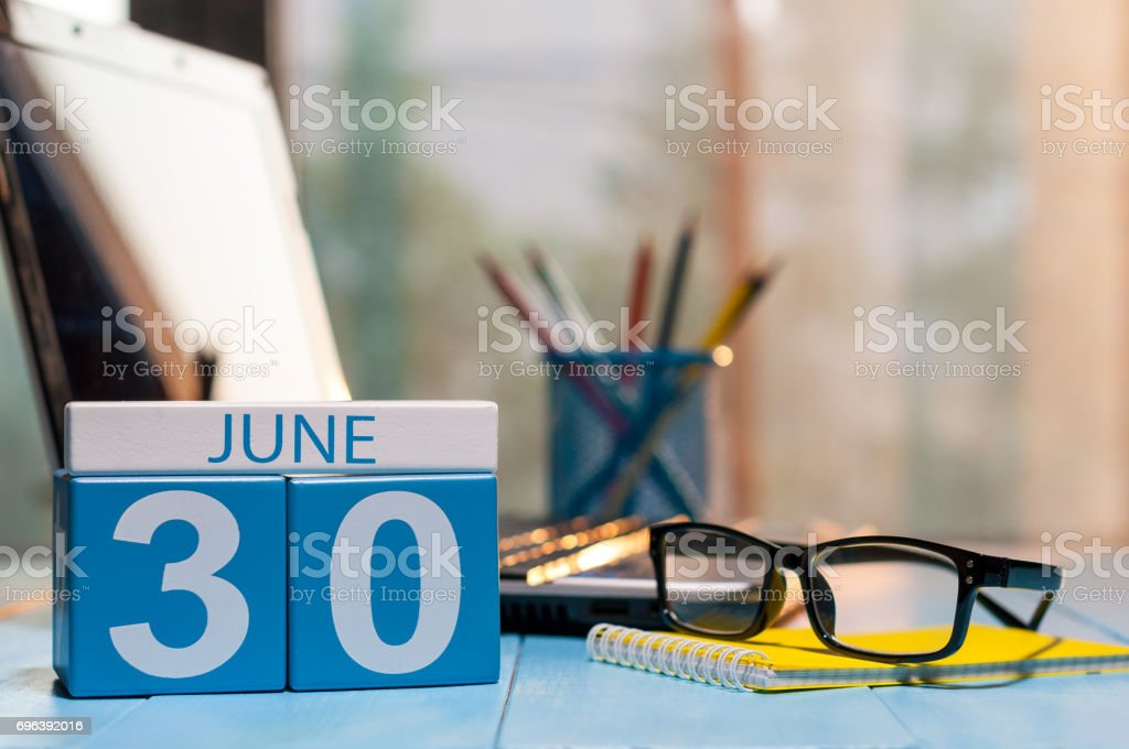 June 30th. Day 30 of month, wooden color calendar on manager workplace background. Summer time. Empty space for text stock photo