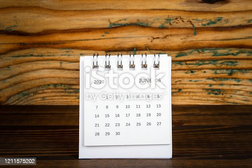 816405814 istock photo 2020 June. White paper calendar on a wooden table 1211575202