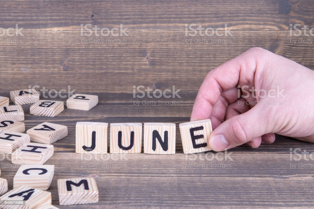 June. Wooden letters on the office desk stock photo