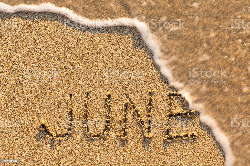 June - word drawn on the sand beach stock photo
