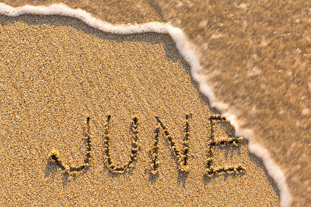 june - word drawn on the sand beach - june stock photos and pictures