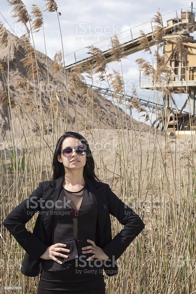Junge Frau vor Förderanlage und Schilf stock photo