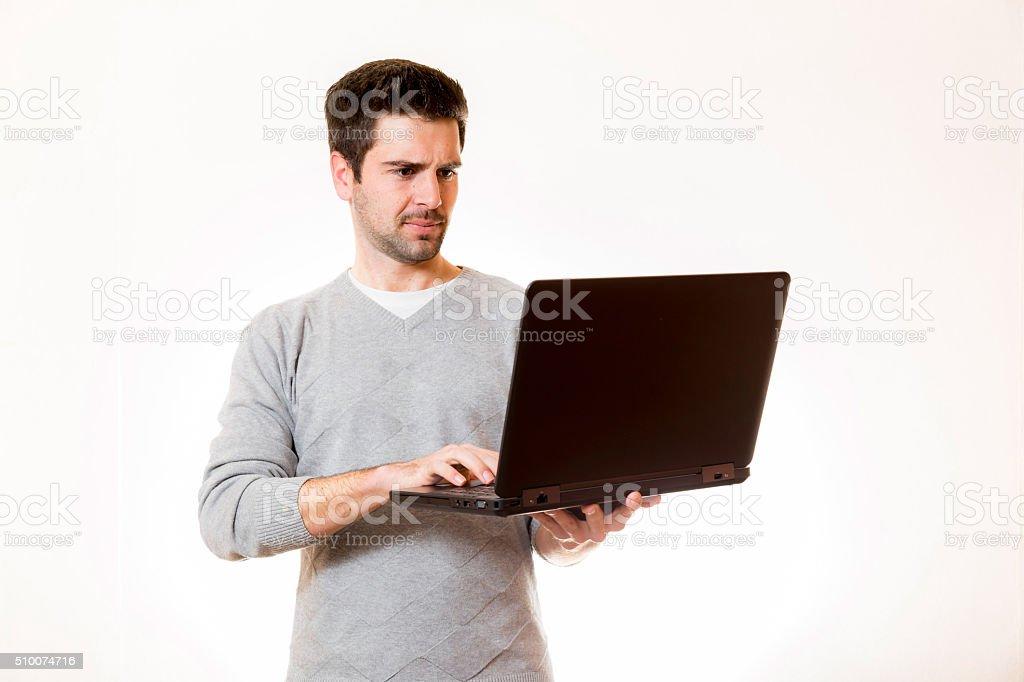 Junger Mann arbeitet im Stehen an einem Laptop stock photo