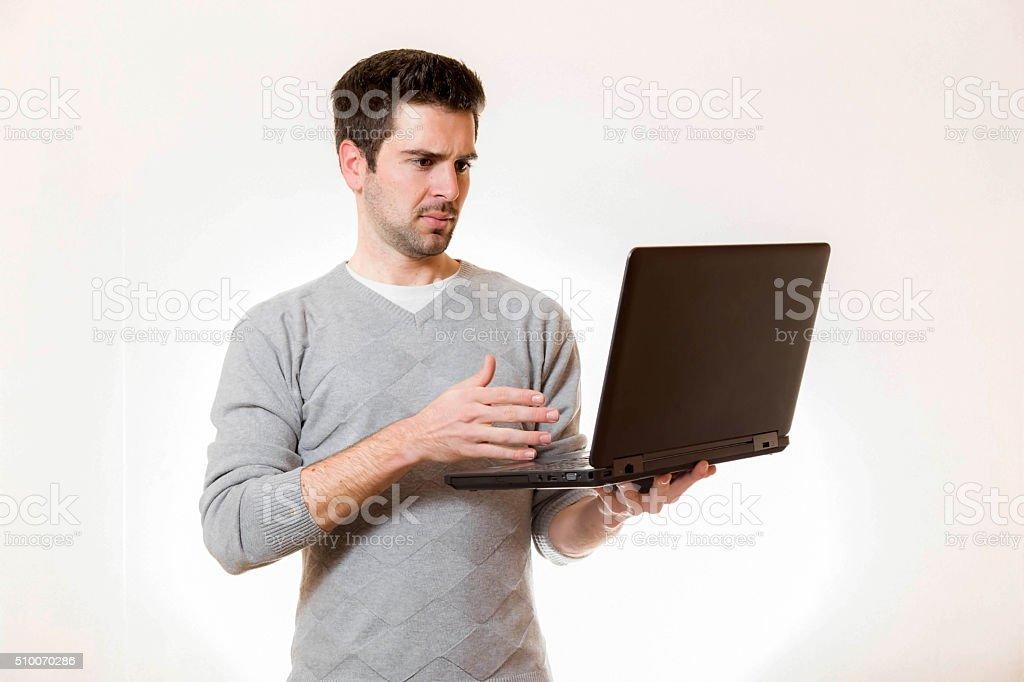 Junger Mann schaut mistrauisch auf einen Laptop stock photo