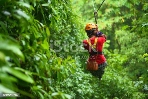 An explorer is moving on cableway in the rainforest