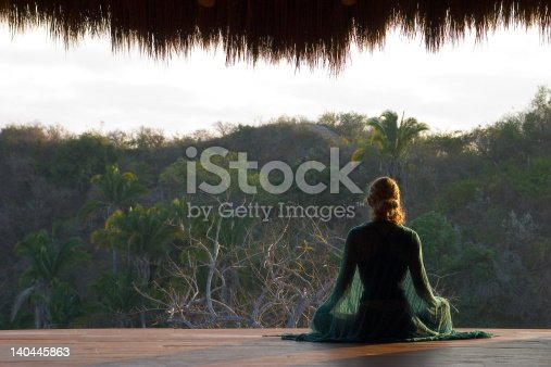 A woman meditates in early morning facing a tropical jungle.