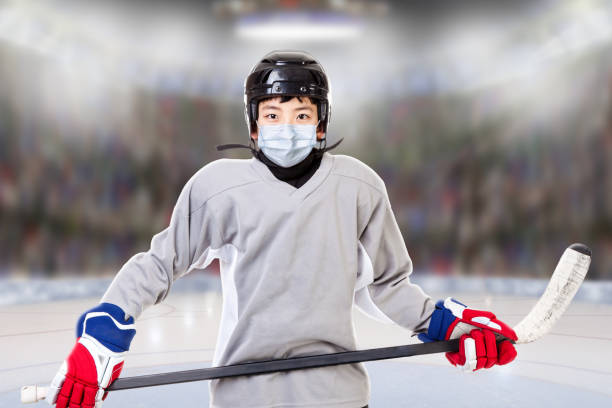 Junior Boy Ice Hockey Player Wearing Face Mask in New Normal After Covid-19 stock photo