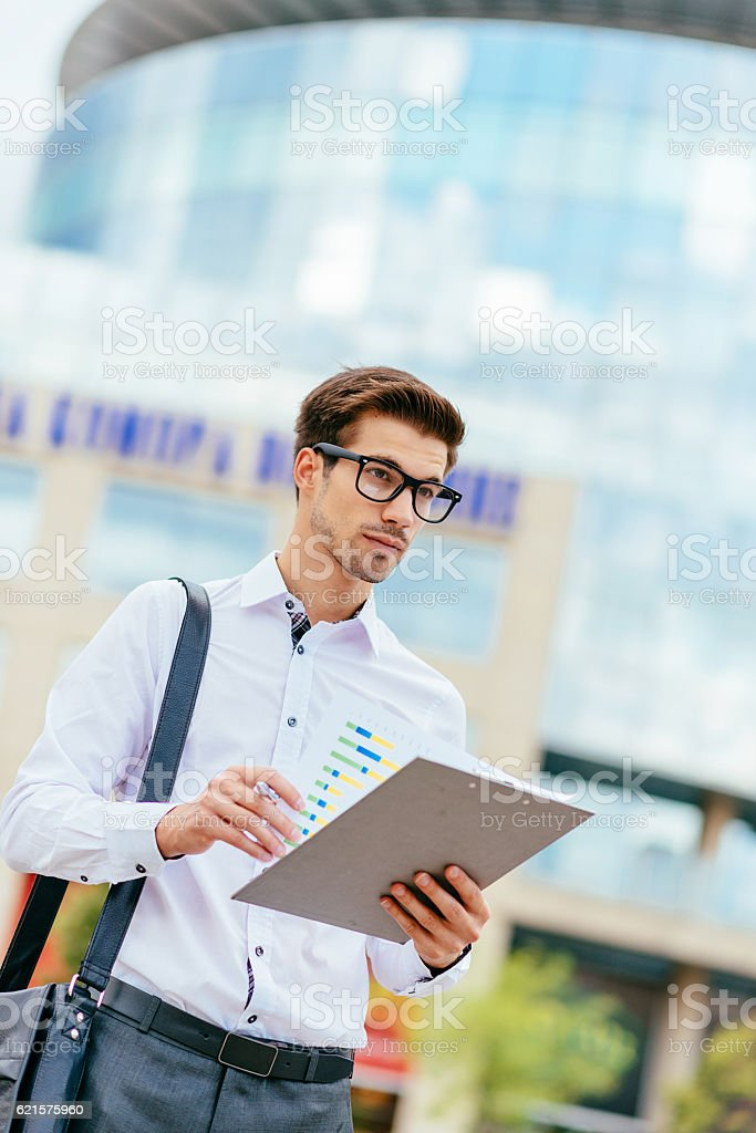 Junior business person with graphs on market demands photo libre de droits