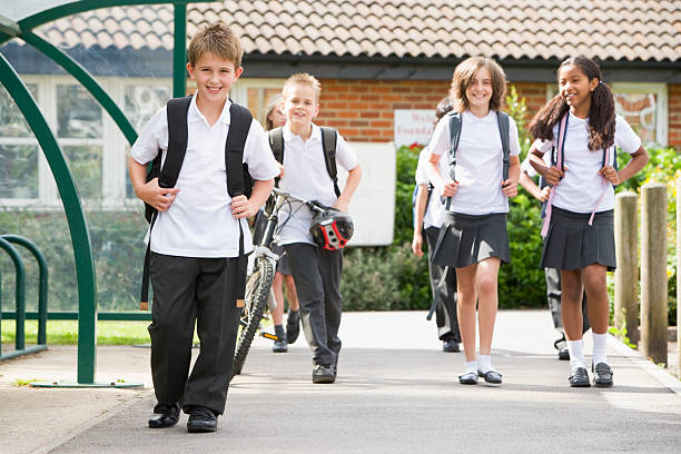 Junior children leaving school stock photo
