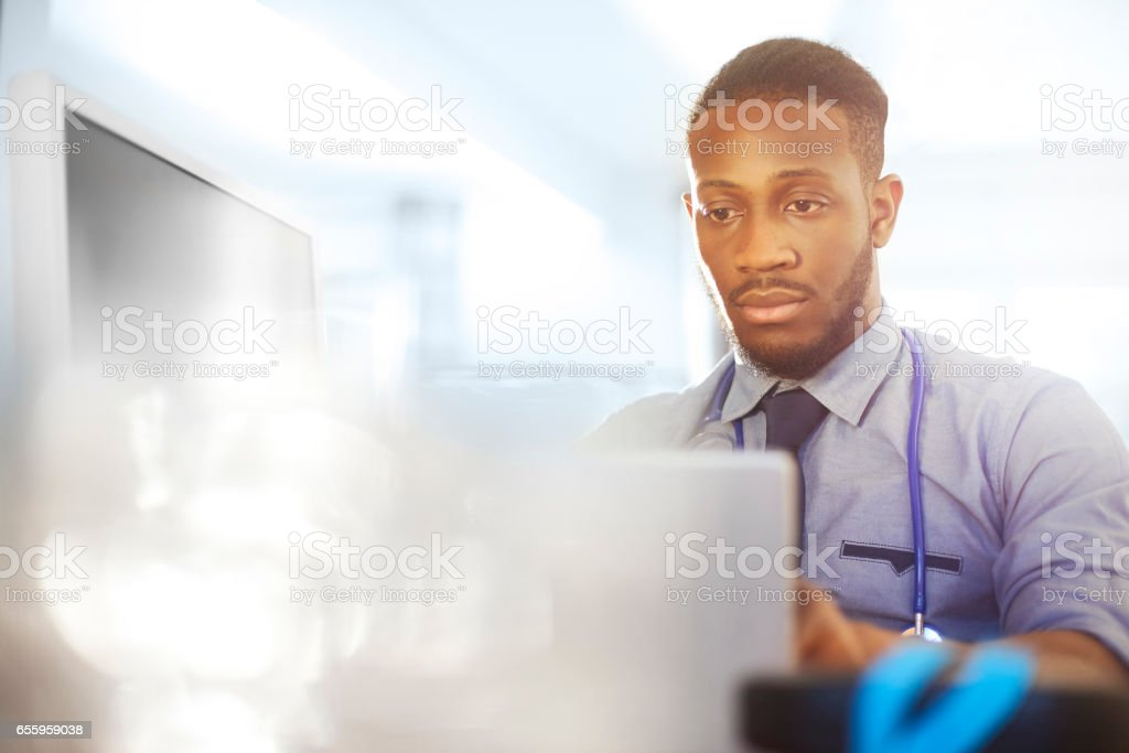Junior doctor working at his desk in his office stock photo