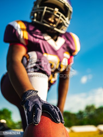 African American Junior Football player getting during game practice at the outdoor field.