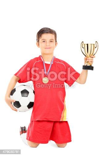 istock Junior de retención de bola de un jugador de fútbol y de la copa de  · istock Retrato de cuerpo entero ... 6f363269255ea
