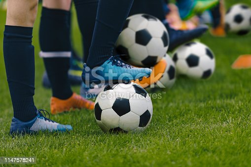 istock Junior Football Training Session. Players Standing in a Row with Classic Black and White Balls. Youths Practice on Soccer Field. Low Angle Close-up Image of Soccer Boys. Football Education Background 1147578241