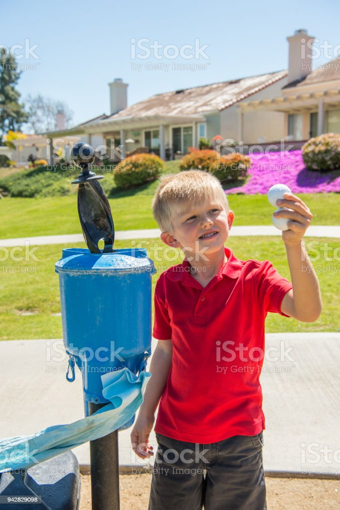 Junior Golfer Cleaning His Golf Ball stock photo