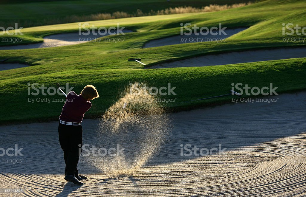 Junior Golfer Hitting Bunker Shot stock photo