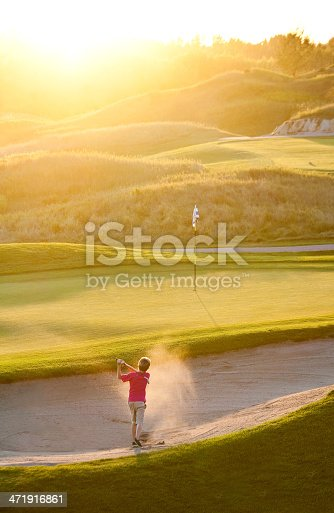 istock Junior Golfer Hitting Bunker Shot 471916861