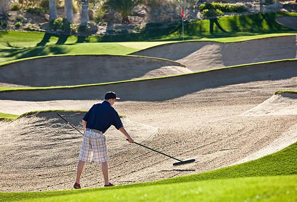 Junior Golfer Raking Bunker