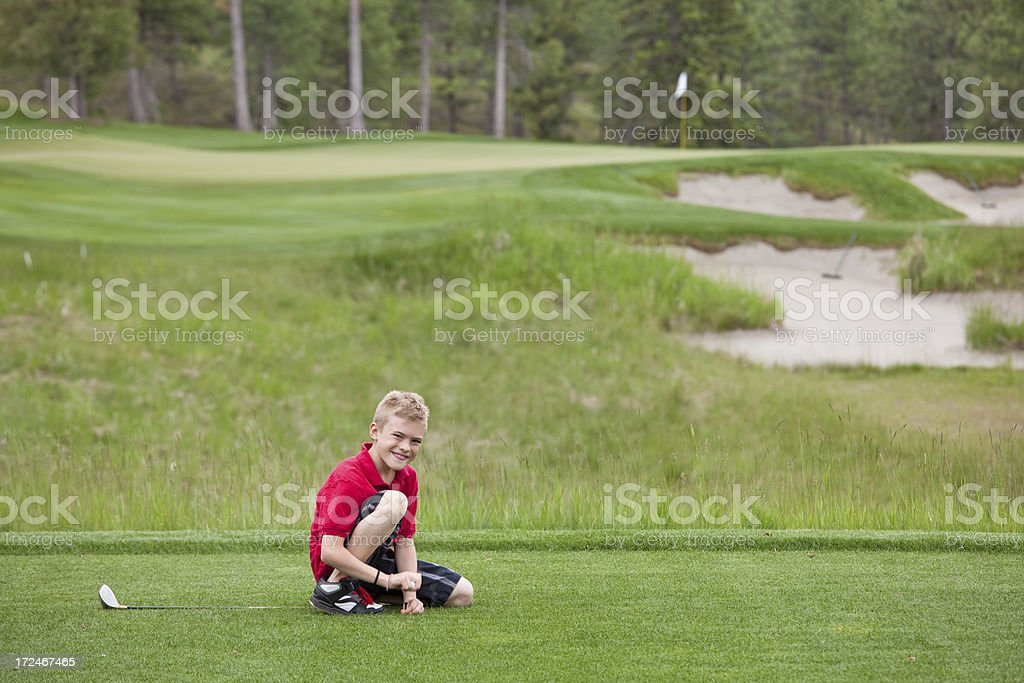 Junior Golfer Teeing Up His Ball royalty-free stock photo