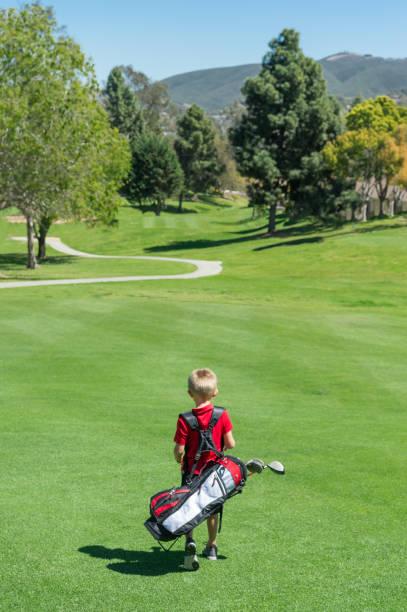 Junior Golfer Walking To The Green stock photo
