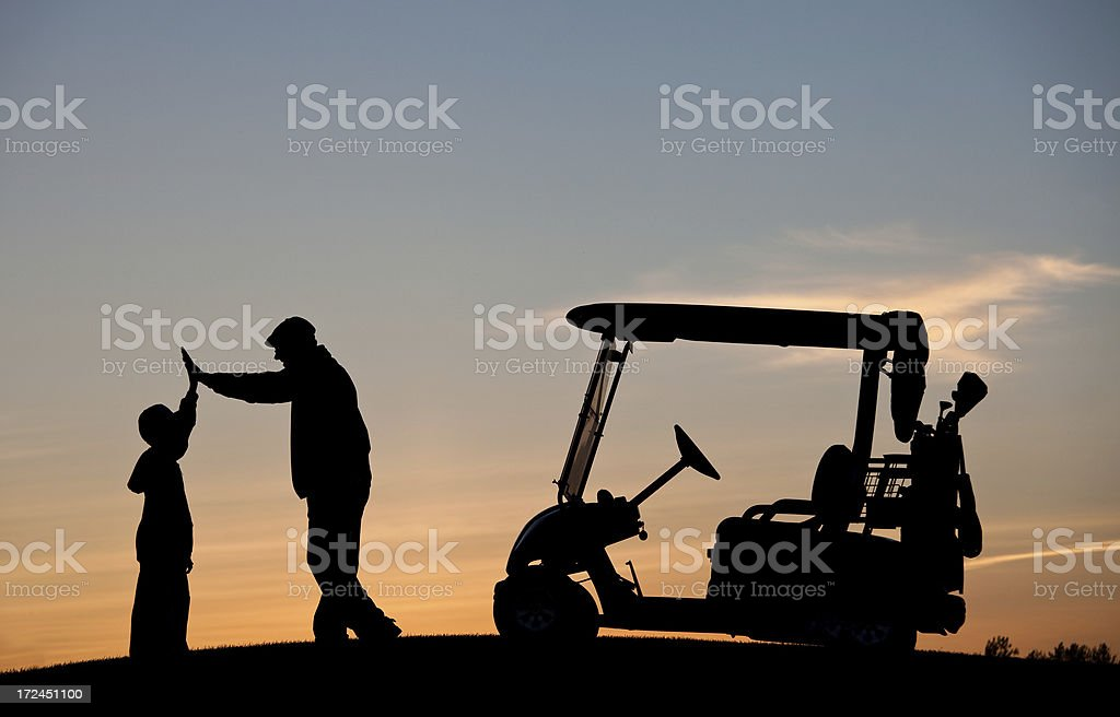 Junior Golfer With Grandfather High Fiving stock photo
