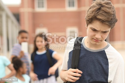 Sad, junior high school age boy being bullied outside the school building,  A group of multi-ethnic students in background laugh at the boy.  They have mobile devices to cyber bully the child as well as point and talk about him.