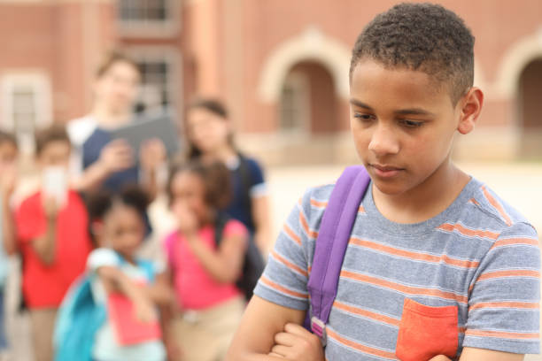 Junior high age boy being bullied at school. stock photo