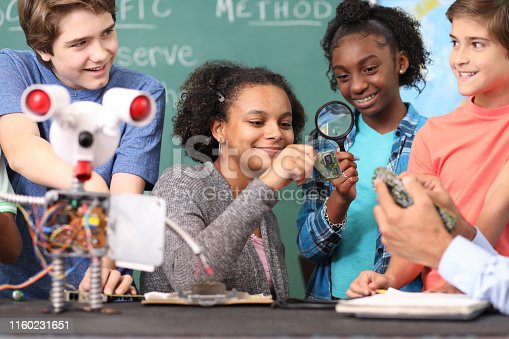 1016655140 istock photo Junior high age school students build robot in technology, engineering class. 1160231651