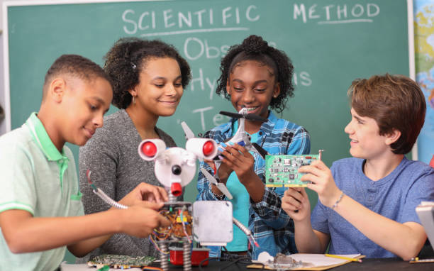 Junior high age school students build robot in technology, engineering class. stock photo