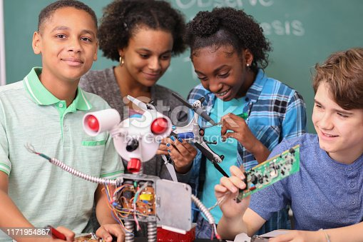 1016655140 istock photo Junior high age school students build robot in technology, engineering class. 1171954867