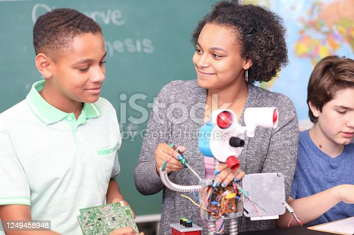 1016655140 istock photo Junior high age school students build robot in technology, engineering class. 1249458948