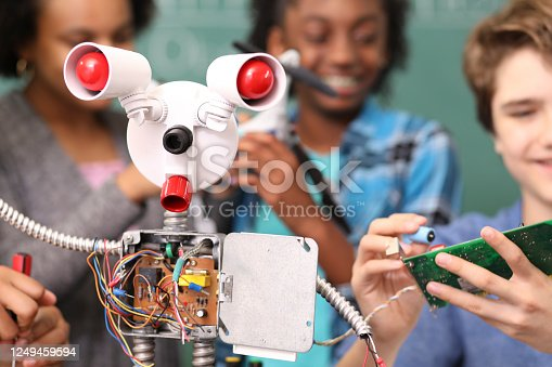 1016655140 istock photo Junior high age school students build robot in technology, engineering class. 1249459594