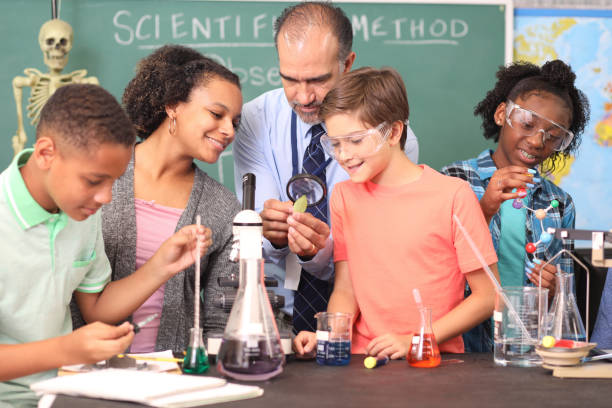 Junior high age school students conduct science experiments in classroom. stock photo