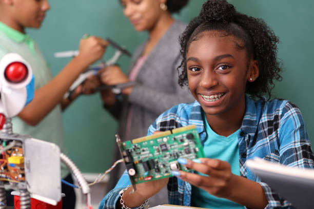 Junior high school age school students build robot in technology, engineering class. stock photo