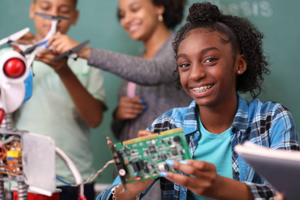 Junior high school age school students build robot in technology, engineering class. stock photo