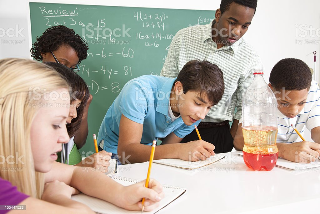 Junior high students, African descent teacher in science classroom. Education. stock photo
