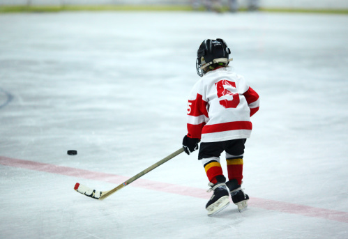 Rear view of unrecognizable 6 year old boy at ice hockey practice trying to reach the puck. He's wearing black helmet and white and red jersey and red socks.