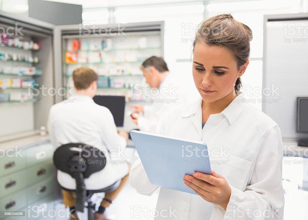 Junior pharmacist using tablet pc stock photo