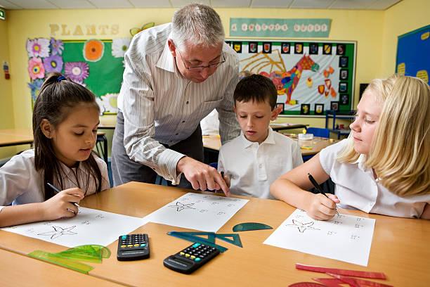 junior school: Lehrer helfen Schüler mit seinen ersten Jahren Mathematik – Foto