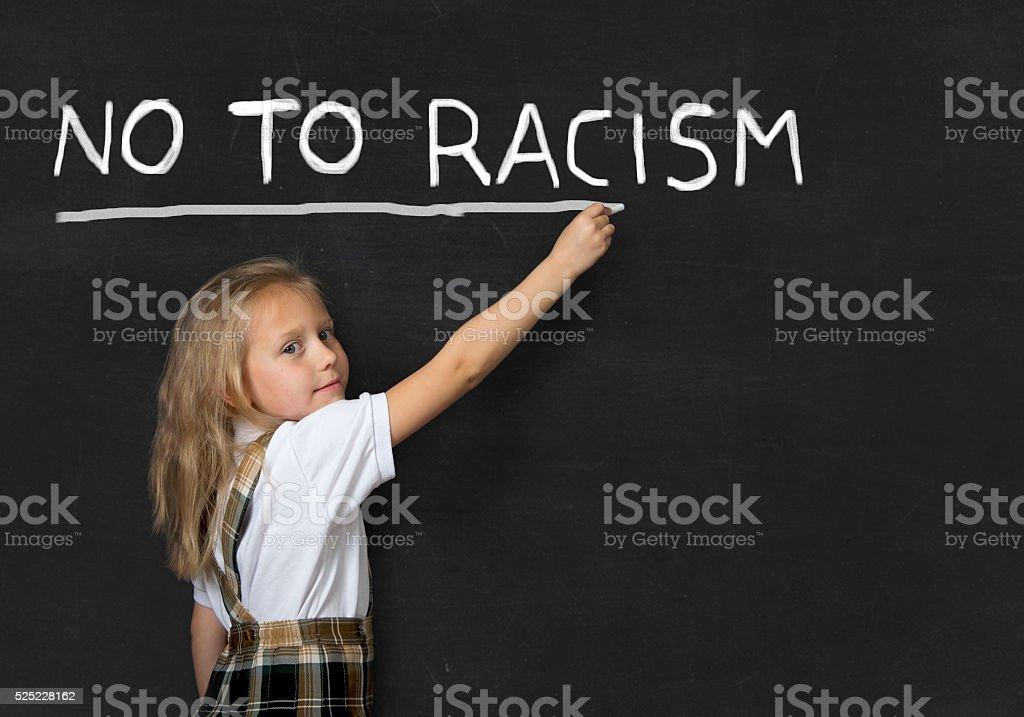junior schoolgirl writing no to racism in school classroom blackboard stock photo
