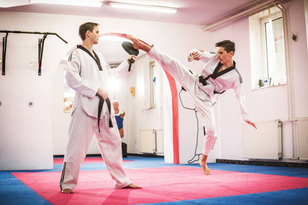 Junior taekwondo trainee kicking focus pad stock photo