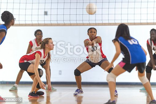 A volleyball match between high school girl's teams in an indoor gym. The team in red-and-white jerseys are about to bump the ball.