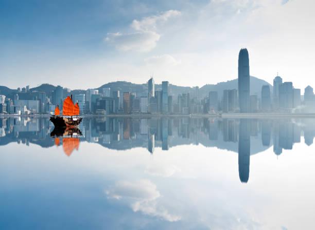 junk boat crossing hong kong harbor - asia orientale foto e immagini stock