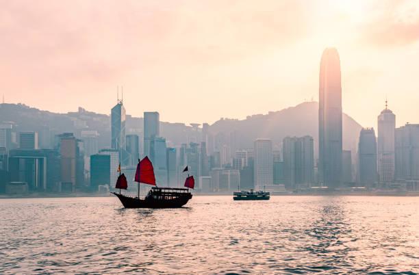 dschunke in hongkong am victoria harbour am abend - kowloon stock-fotos und bilder