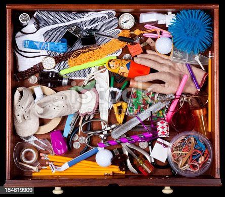 Junk Drawer with miscellaneous objects, Including, Baby Shoes Elastic Bands, Pencils, Compass, New Years Eve Party Blower, Fake Hand, Cellophane Tape, and More. Image shot with, Canon 5D Mark2 , 100 ISO, 24-115mm lens and studio strobes.