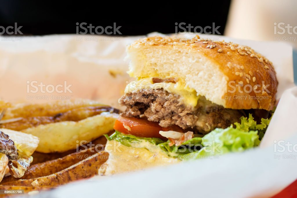 Junk food background: Half blue cheese burger with beef and vegetables on white paper with golden potato stock photo