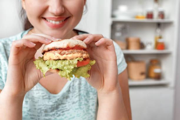 Junk food chubby girl sitting at kitchen eating hamburger smiling picture id1190059426?b=1&k=6&m=1190059426&s=612x612&w=0&h=nhv2objvcpdhkbatmvckauxeea8qlw8tqtjlgs zqwq=