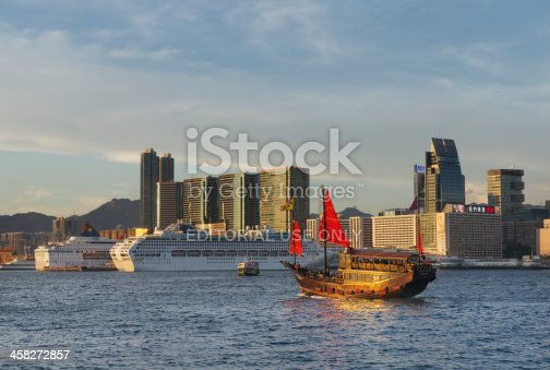 Hong Kong, China - July 30, 2013: A (replica of an old) Chinese Junk Ship with red sails crosses the Victoria Harbour towards Kowloon - with skyscrapers and large cruise ships - as the sun sets in west.