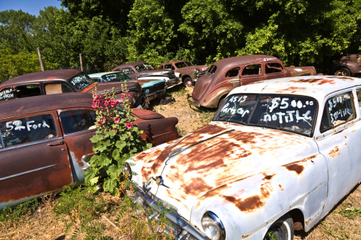 Glendale, USA - July 17, 2008: junk yard with old rotten rusty classic cars in Glendale, USA. the price of the wrecks is written on the window shield. The classic car wrecks stand on a field without any weather protection.