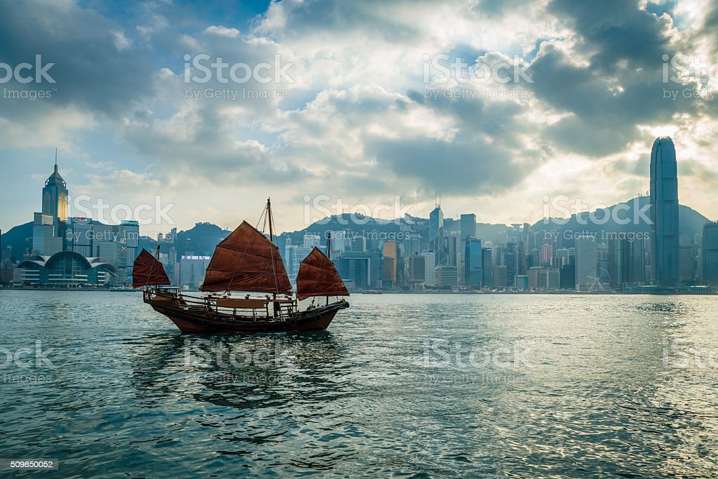 HK Junkboat sailing along Hong Kong Skyline stock photo